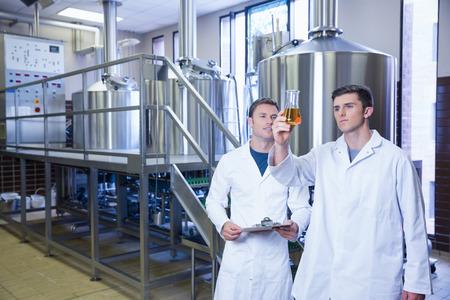 bata de laboratorio: Dos hombres en bata de laboratorio mirando el vaso con cerveza en la f�brica