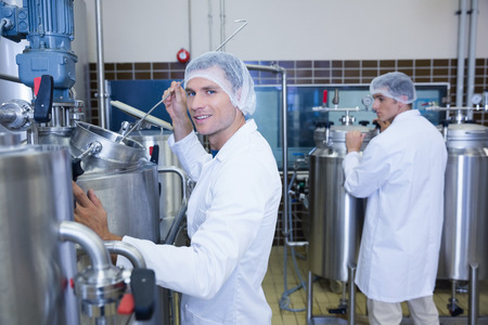 microbrewery: Scientist working and smiling at camera in the factory