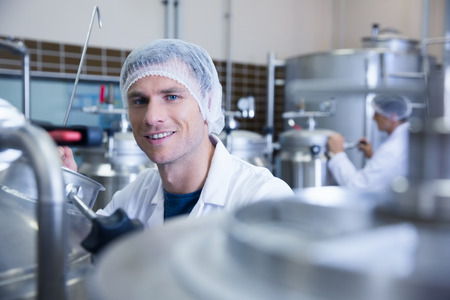 microbrewery: Close up of a man wearing a hair net looking at the camera in the factory Stock Photo