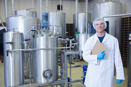 food industry: Man holding a clipboard standing in front of the container in the factory Stock Photo