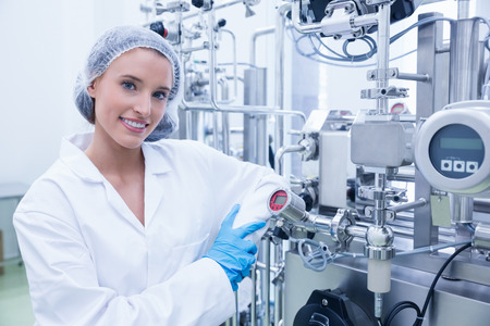 industries: Smiling scientist leaning against gauge in the factory Stock Photo