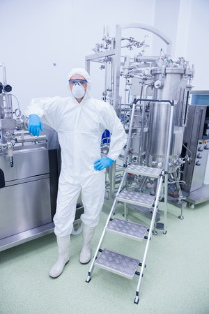 microbrewery: Scientist in protective suit leaning against machine in the factory