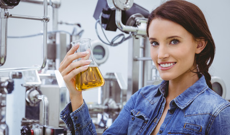 microbrewery: Smiling woman holding a beaker of beer in the factory
