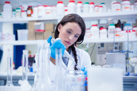 lab coats: Concentrated female scientist using a pipette in hospital