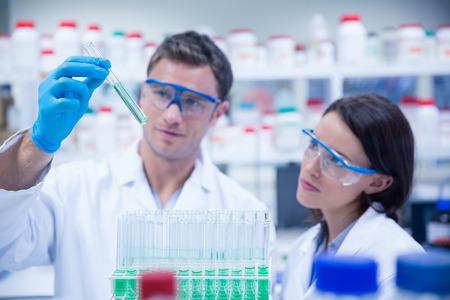 laboratory coat: Smiling chemist holding test tube containing liquid in the laboratory Stock Photo