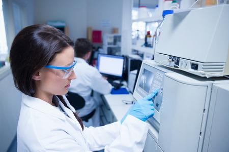 Jonge chemicus gebruik van de machine in het laboratorium