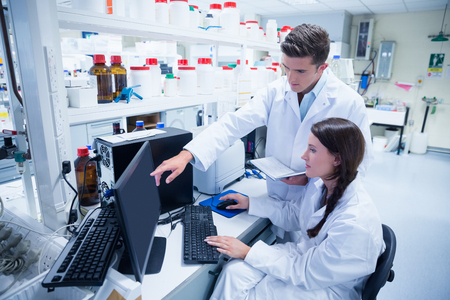Chemist team working together at desk using computer in the laboratory Stockfoto
