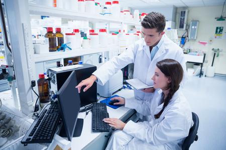 laboratorio: Equipo qu�mico trabajando juntos en el escritorio usando la computadora en el laboratorio