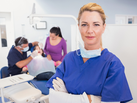 dental nurse: Dentist with folded arms with patient behind her