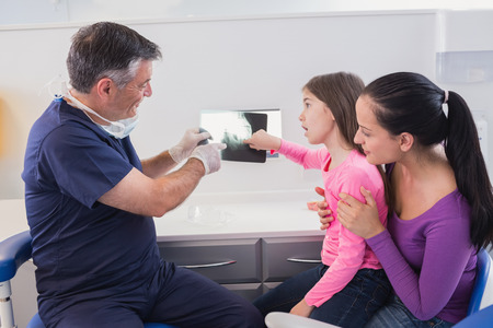 pediatric: Pediatric dentist explaining to young patient and her mother the x-ray in dental clinic Stock Photo