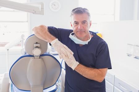 odontologo: Dentista sonriente que se inclina contra la silla de los dentistas en la clínica dental