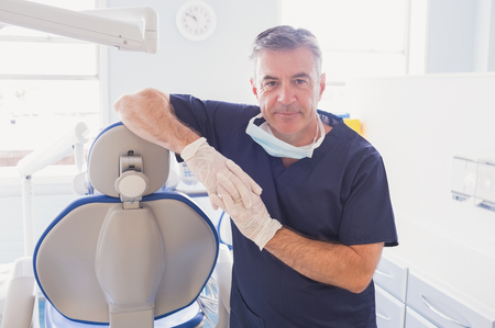 dentist at work: Smiling dentist leaning against dentists chair in dental clinic