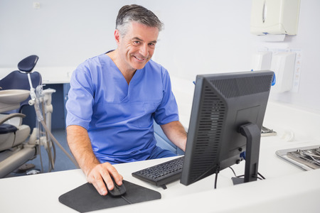 Portrait of a happy dentist using computer in dental clinic