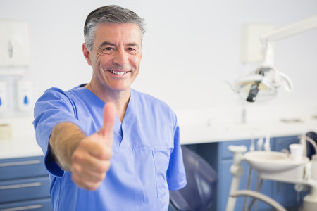 dental clinics: Portrait of happy dentist with thumbs up in dental clinic