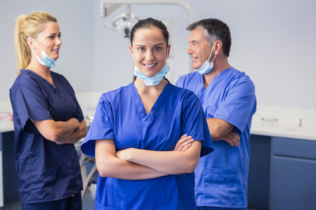 Smiling co-workers talking with arms crossed in dental clinic