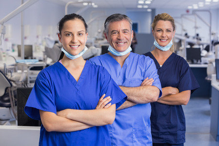 dental nurse: Portrait of smiling co-workers in a line with arms crossed in dental clinic Stock Photo