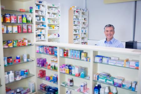 farmacia: Farmacéutico con el pelo gris de pie detrás de los estantes de los medicamentos en la farmacia Foto de archivo