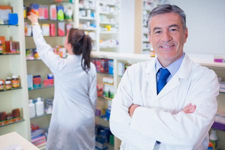 farmacia: Farmac�utico que mira la c�mara con el estudiante detr�s de �l en la farmacia