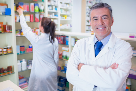 arms crossed: Pharmacist looking at camera with student behind him in the pharmacy Stock Photo