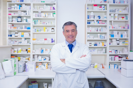 Smiling pharmacist standing with arms crossed in the pharmacy