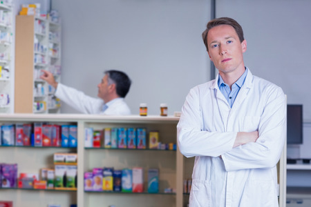unsmiling: Unsmiling pharmacist standing with arms crossed in the pharmacy