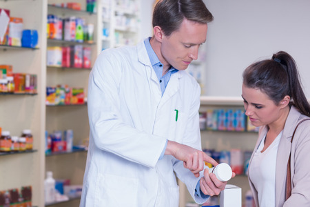 Pharmacist explaining the pills to patient in the pharmacy