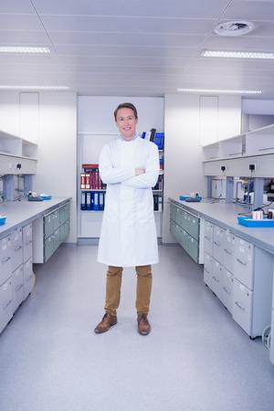 biochemist: Smiling biochemist standing with arms crossed in laboratory Stock Photo