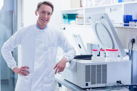 centrifuge: Smiling chemist leaning against the centrifuge in laboratory