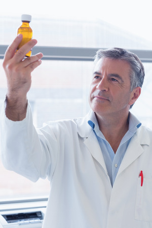 chemical bottle: Smiling scientist in lab coat holding a chemical bottle in laboratory Stock Photo