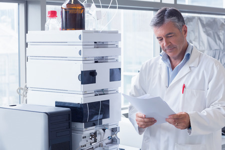 과학자는 실험실에서 분석을 읽고 실험실 코트 서