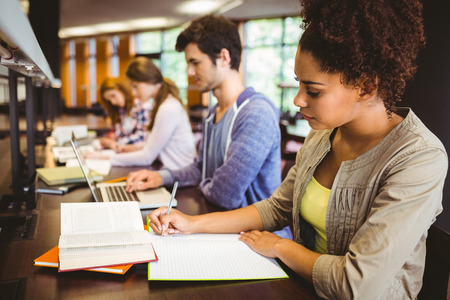 Focused students sitting in a line writing in library Foto de archivo
