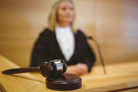 mandato judicial: Juez serio con un martillo que llevaba vestiduras en la sala del tribunal
