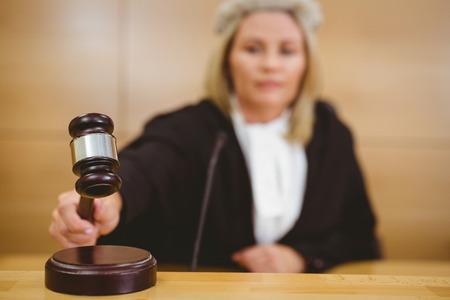 orden judicial: Juez serio con un martillo vestidos con túnicas y peluca en la sala del tribunal