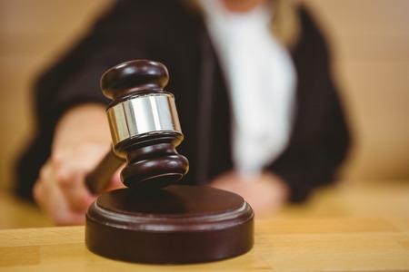 orden judicial: Mano a punto de golpear el martillo en bloque de sondeo en la sala del tribunal