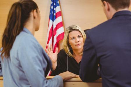 orden judicial: El juez y los abogados hablar delante de la bandera americana en la sala del tribunal Foto de archivo