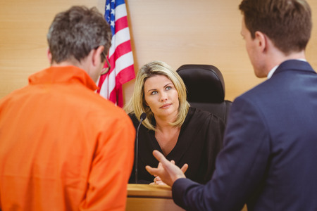 judges: Lawyer speaking about the criminal in orange jumpsuit in the court room Stock Photo