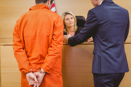 derecho penal: Abogado y juez habla al lado del penal esposado en la sala del tribunal Foto de archivo