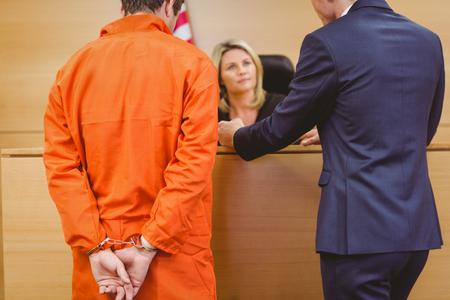 Advocaat en rechter spreken naast de misdadiger in handboeien in de rechtszaal