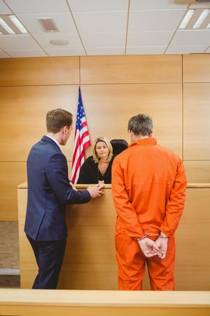 orden judicial: Abogado y juez hablando junto a la penal en mono en la sala del tribunal