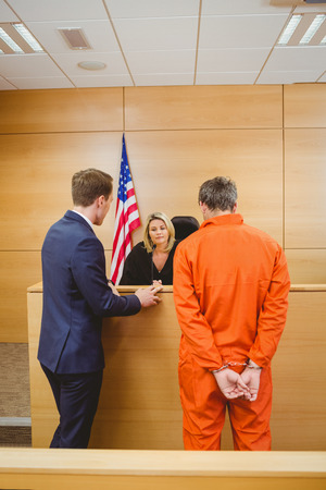 Lawyer and judge speaking next to the criminal in jumpsuit in the court room