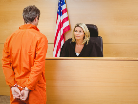 sentencing: Judge and criminal speaking in front of the american flag in the court room Stock Photo