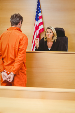 Judge and criminal speaking in front of the american flag in the court room photo