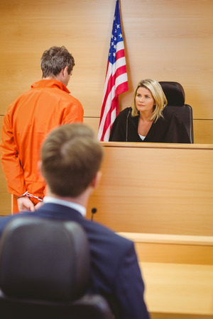 female judge: Judge and criminal speaking in front of the american flag in the court room Stock Photo