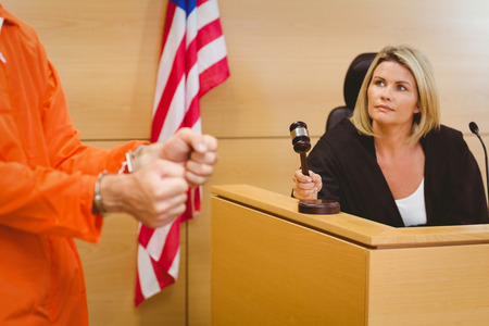 female judge: Judge about to bang gavel on sounding block in the court room