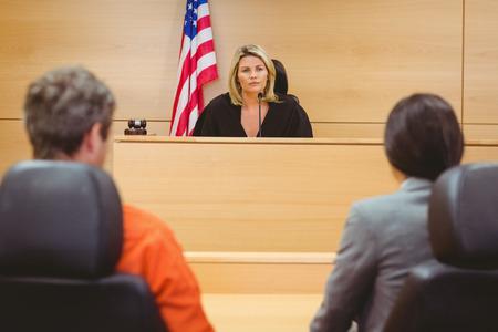 Juge et avocat discuter de la peine pour prisonnier dans la salle d'audience