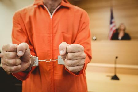 orden judicial: Preso en manillas apretando los puños en la sala del tribunal