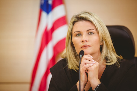 female judge: Portrait of a serious judge with american flag behind her in the court room