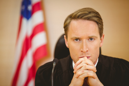 trial indoor: Portrait of a serious judge with american flag behind him in the court room