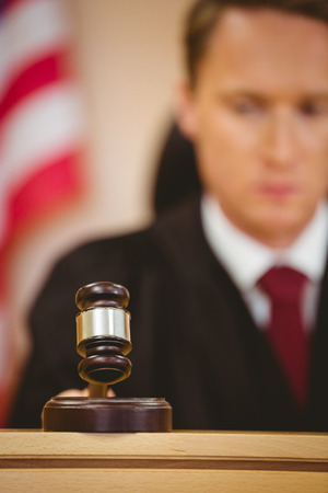 trial indoor: Serious judge about to bang gavel on sounding block in the court room
