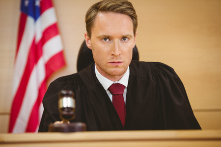 banging: Portrait of a judge about to bang gavel on sounding block in the court room
